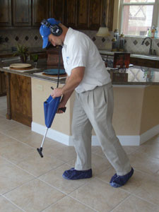 Checking below a kitchen's tiles during a leak detection in Fresno